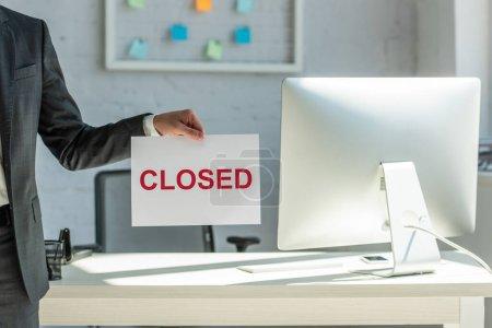 Photo pour Vue recadrée de l'homme d'affaires tenant signe avec lettrage fermé avec lieu de travail flou sur fond - image libre de droit