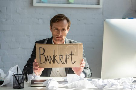 Upset businessman holding cardboard with bankrupt lettering, while sitting at workplace with crumpled papers