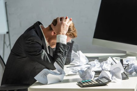 Stressed businessman with hands on head, sitting at workplace with crumbled papers on blurred background