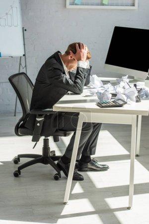 Die ganze Länge des deprimierten Geschäftsmannes mit den Händen auf dem Kopf, der mit zerbröckelten Papieren am Arbeitsplatz sitzt