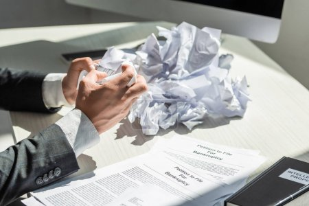 Cropped view of businessman holding crumbled paper near petitions for bankruptcy at workplace on blurred background