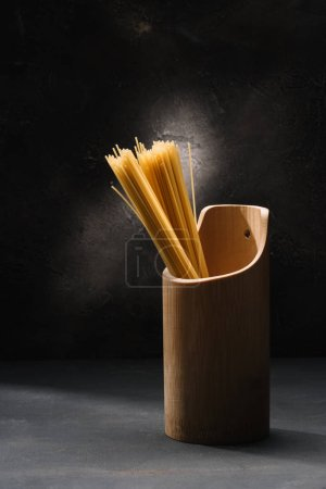 Photo for Bunch of uncooked spaghetti in wooden container with garlic on black surface - Royalty Free Image