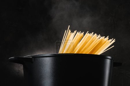 Photo for Spaghetti boiling in black pan on dark background - Royalty Free Image