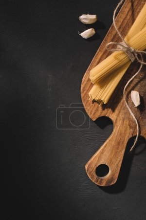 top view of tied spaghetti with garlic on wooden cutting board