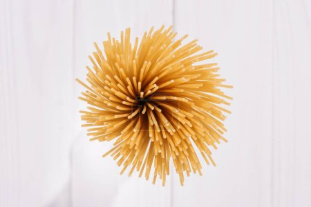 top view of bunch of raw spaghetti on white wooden surface