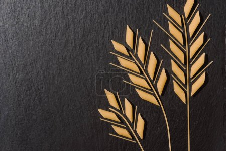 Photo for Top view of wheat ears made of raw pasta on black surface - Royalty Free Image
