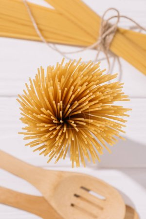 top view of bunch of raw spaghetti on white wooden tabletop with kitchenware