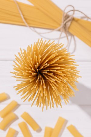 top view of bunch of raw spaghetti on white wooden tabletop