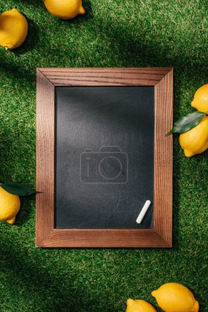 top view of blank chalkboard and lemons with leaves on green lawn
