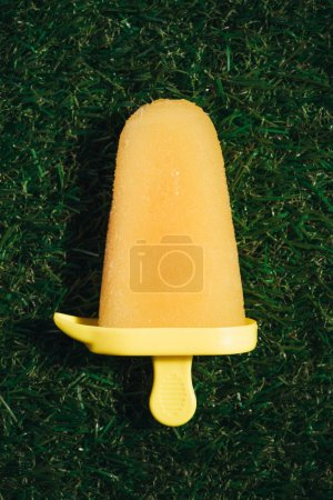 Sweet yellow fruit Popsicle on green grass background