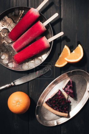 Sweet fruit Popsicles with oranges and berry pie on wooden background