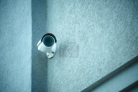 close up view of security camera on gray building facade
