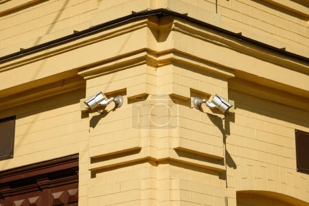 closeup image of security cameras on yellow building facade in sunlight