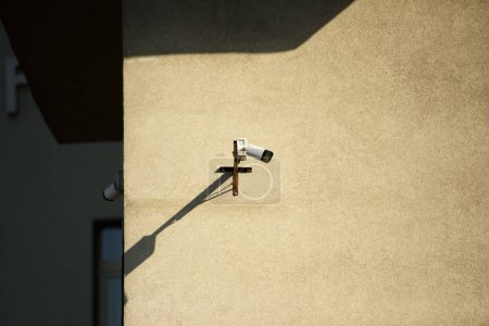 close up view of security camera on building facade in sunlight