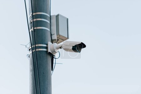 close up view of security camera on street pole with blue sky on background