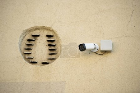close up view of security camera on cracked building facade