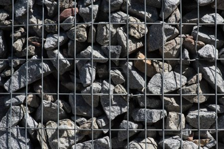 full frame image of metal cage covered stones background