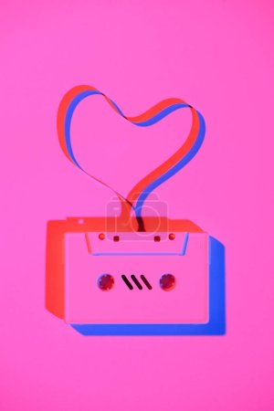toned pink picture of retro audio cassette with tape in heart shape on tabletop