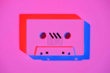 toned pink picture of retro audio cassette on pink surface