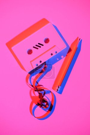 toned pink picture of retro audio cassette with pencil and tape