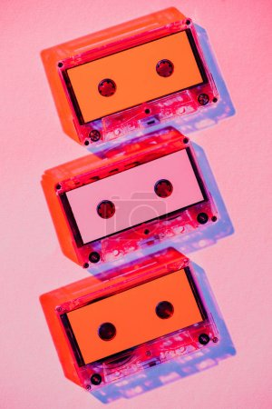 toned picture of colorful retro audio cassettes on pink background