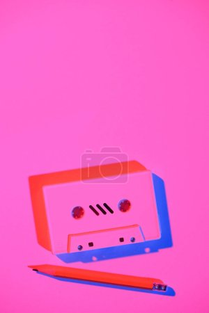toned pink picture of retro audio cassette and pencil