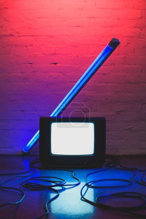 toned picture of arranged retro tv set, cables and lamp with brick wall background