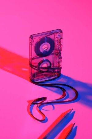 close up view of retro audio cassette and pencils on pink backdrop