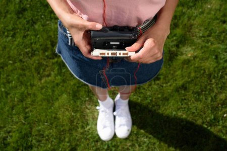 cropped shot of woman with earphones holding retro cassette player with audio cassette in hands while standing on green grass