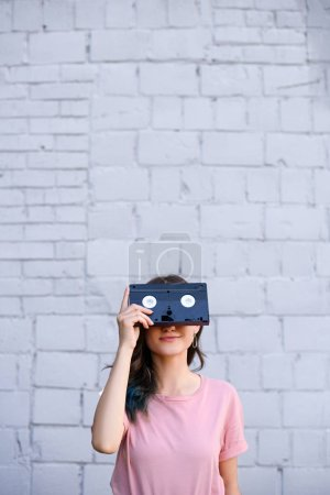 obscured view of woman covering eyes with retro video cassette in hand against white brick wall