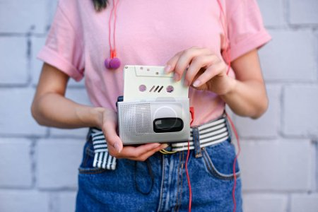 cropped shot of woman with earphones holding retro cassette player and audio cassette in hands against white brick wall