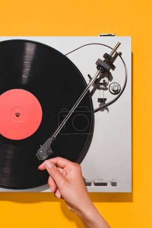 Photo for Cropped shot of woman turning on vinyl player isolated on yellow - Royalty Free Image