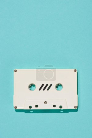 top view of white retro audio cassette isolated on blue