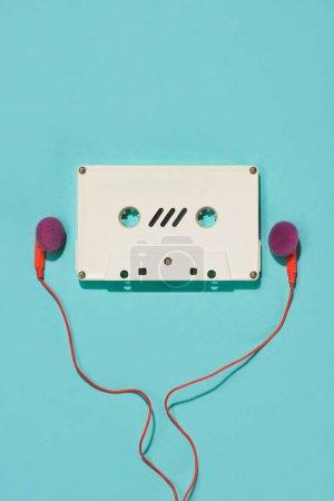 Photo pour Lay plat blanc rétro cassette audio et écouteurs isolés sur bleu - image libre de droit