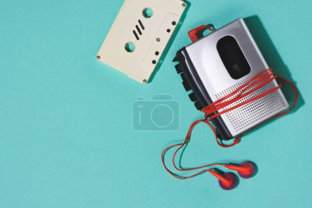 flat lay with retro audio cassette, cassette player and earphones isolated on blue