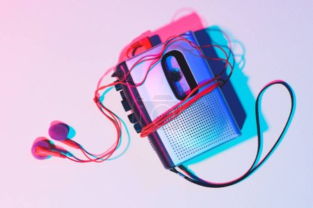 toned picture of retro cassette player and earphones on tabletop