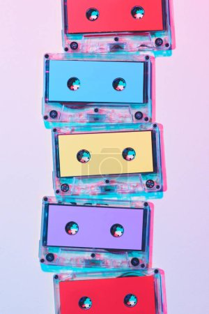 Photo for Top view of arranged colorful audio cassettes on purple background - Royalty Free Image