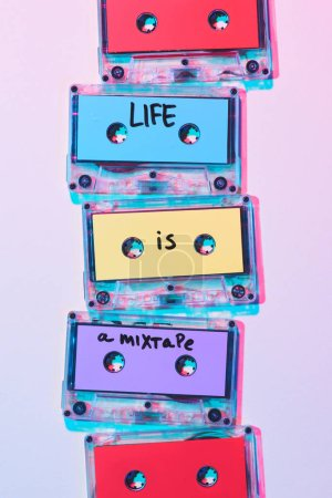 Photo for Top view of arranged colorful audio cassettes with life is a mixtape inscription on purple background - Royalty Free Image