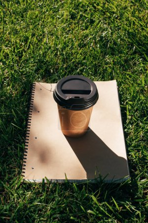 close up view of coffee to go and notebook on green grass