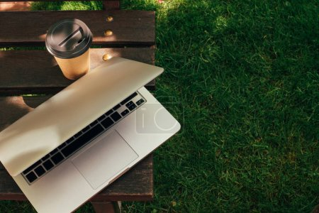 close up view of disposable cup of coffee and laptop on wooden bench