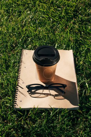 close up view of coffee to go, notebook and eyeglasses on green grass