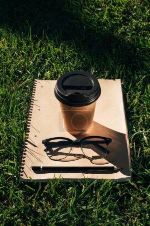 Photo pour Bouchent la vue du café à emporter, pour ordinateur portable avec un crayon et lunettes sur l'herbe verte - image libre de droit