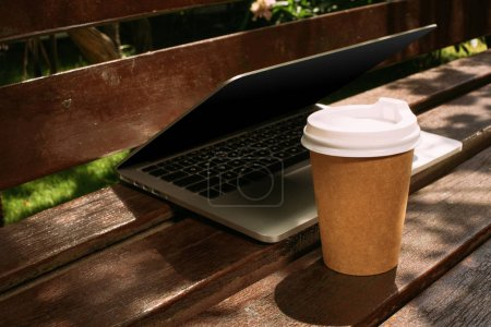 Photo for Close up view of laptop and coffee to go on wooden bench - Royalty Free Image