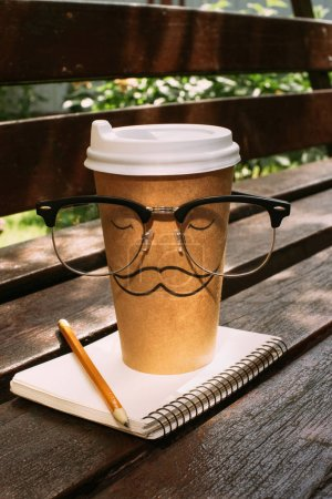 close up view of coffee to go with eyeglasses, notebook and pencil on wooden bench