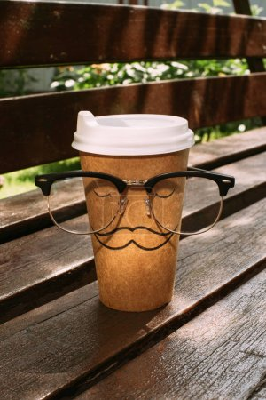 close up view of disposable cup with mustache sign and eyeglasses on wooden bench
