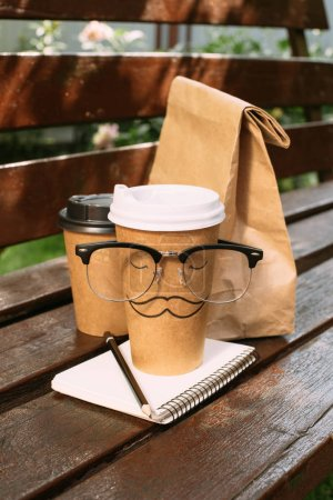 close up view of disposable cups of coffee, paper bag, eyeglasses and notebook on bench