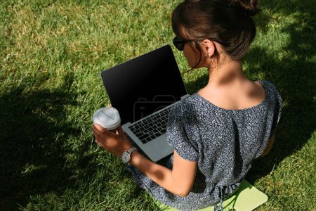 back view of freelancer with coffee to go working on laptop on green lawn in park