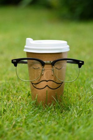 close up view of disposable cup with mustache sign and eyeglasses on green lawn