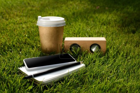 close up view of coffee to go, smartphone, notebook and audio speaker on green grass