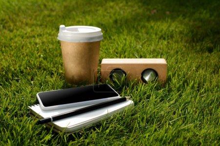 bouchent la vue de café pour aller, smartphone, ordinateur portable et haut-parleur sur l'herbe verte